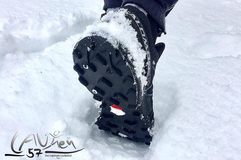 Trail-Laufschuh im Schnee mit grobstolliger Profilsohle.